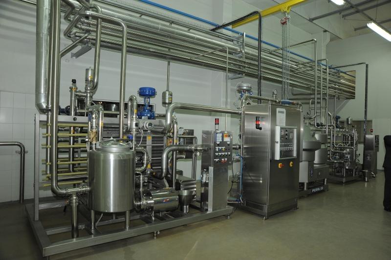 Imagem interna da fábrica mostrando o pasteurizador (mais à esquerda) e a desnatadeira por centrifugação (à direita)
