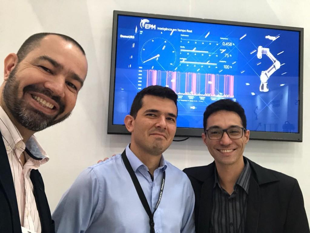 Gustavo Salomão ao lado dos colegas consultores Samir Lima e Thiago Abucarub diante da tela do EPM Portal na feira